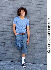 Full body cool young guy with curly hair smiling