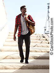 Full body cool young man with bag walking down the steps and looking away