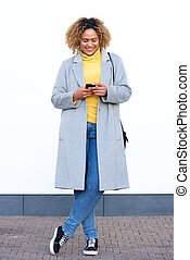 Full body happy young african american woman smiling with cellphone by white wall