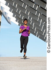 Full body healthy young african woman running outdoors