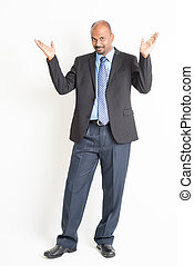 Full body mature Indian businessman open arms and showing something