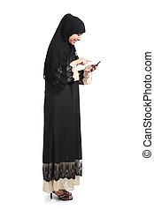 Full body of an arab saudi woman browsing a smart phone