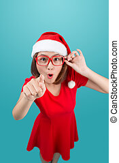 Full-body of attractive cheerful asian girl in Santa's hat pointing with her hand at copy space and happy smiling