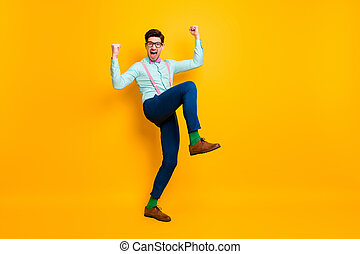 Full body photo of handsome cool clothes guy celebrate quarantine finish rise fists ready chilling party wear specs shirt suspenders bow tie trousers shoes isolated yellow color background