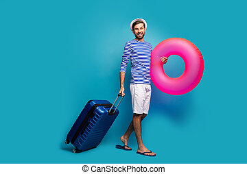 Full body photo of handsome guy traveler hold rolling case round big pink lifebuoy arrive sun country wear striped sailor shirt cap shorts flip flops isolated blue color background