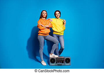 Full body photo of two ladies with vintage tape recorder going to chill party with modern rhythms wear casual orange yellow hoodies isolated blue color background
