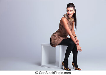 elegant fashion woman sitting on a chair while smiling