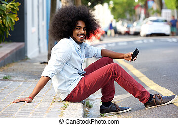 happy man with mobile phone sitting on sidewalk