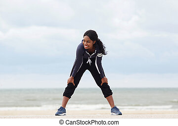healthy young african american woman resting with hands on knees at the beach