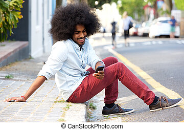 smiling young man with mobile phone sitting on sidewalk