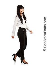 Full body portrait of walking businesswoman