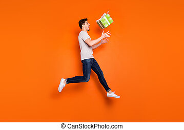 Full body profile photo of funny guy jump high up catch big green giftbox lucky birthday present wear striped t-shirt jeans sneakers isolated bright orange color background