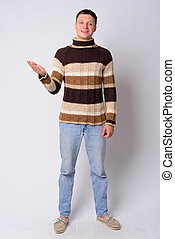 Full body shot of happy young man showing something ready for winter