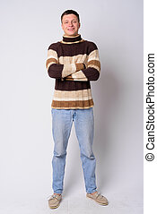 Full body shot of happy young man smiling with arms crossed ready for winter