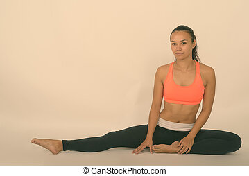 Full body shot of young Asian woman stretching her right leg while sitting on the floor against white background