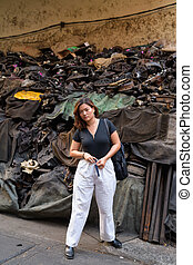 Full body shot of young beautiful Asian tourist woman in dirty alley