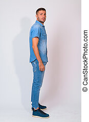 Full body shot profile view of handsome bearded Persian man standing and looking at camera