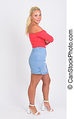 Full body shot profile view of young beautiful blonde woman looking at camera