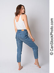 Full body shot profile view of young beautiful woman looking over shoulder