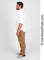 Full body shot profile view of young handsome bearded Indian man
