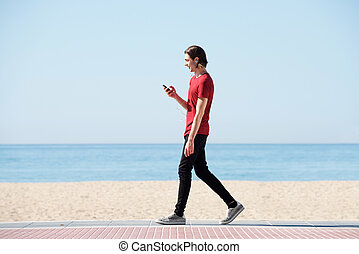 Full body side of handsome man walking by sea with smart phone