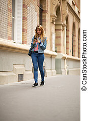 Full body young woman walking in city looking at mobile phone