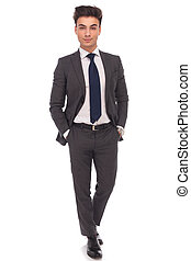 confident business man standing with hands in pockets