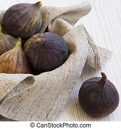 Full bowl of fresh figs on a white wooden background, side view. Close-up.