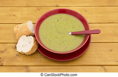 Full bowl of soup with slices of baguette