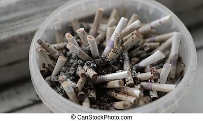 full bucket of cigarette butts.