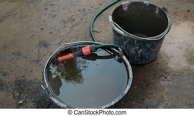 full bucket of water and a hose at the construction site....