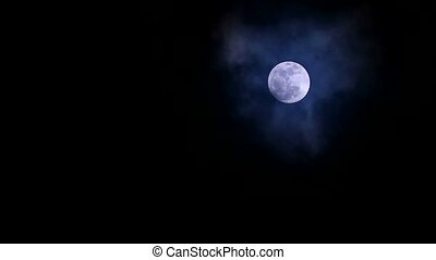 Full cold moon in the night sky soft and dark cloud moving pass