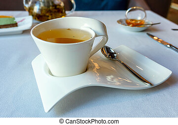 full Cup of green herbal tea on a white plate of unusual form