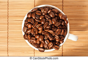 Full cup with coffee beans on the table