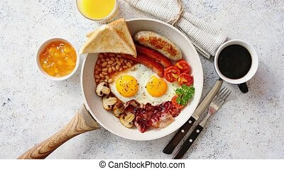Full English Breakfast served in a pan. Fried eggs, beked ...