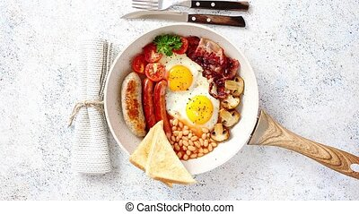 Full English Breakfast served in a pan. Fried eggs, beked...