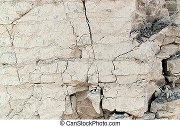 full frame light brown cracked rock face background