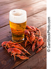 Full glass of beer with boiled crawfish on the table