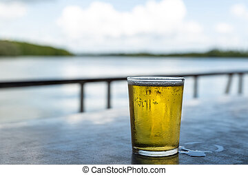 full glass of cold beer is standing on the table of a summer cafe closeup with copy space