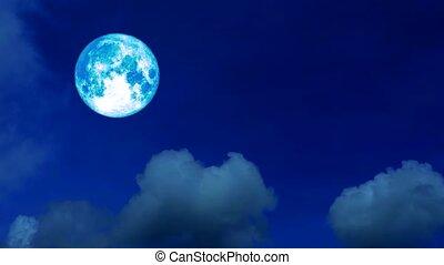 full harvest blue moon moving pass back cloud on dark night sky