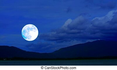full harvest moon rise on night sky and back mountain and lake