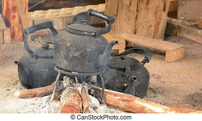 Full HD video - Three blackened, sooty, tea kettles resting over the glowing coals of a smoldering cooking fire.