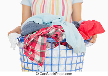 Woman in apron carrying full laundry basket