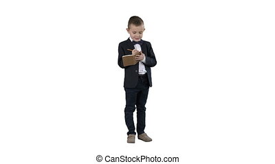 Full lenght shot. Boy in a formal clothes writing in check list or notebook on white background. Professional shot in 4K resolution. 016. You can use it e.g. in your commercial video, education, business, presentation, broadcast