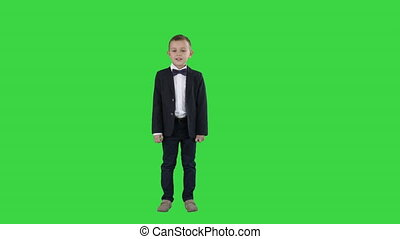 Full lenght shot. Boy in a suit walks in a frame and starts talking on a Green Screen, Chroma Key. Professional shot in 4K resolution. 016. You can use it e.g. in your commercial video, education, business, presentation, broadcast