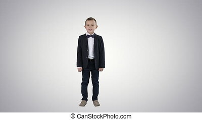 Full lenght shot. Boy in a suit walks in a frame and starts talking on gradient background. Professional shot in 4K resolution. 016. You can use it e.g. in your commercial video, education, business, presentation, broadcast