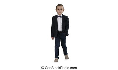 Boy in formal costume walking with a hand in pocket on white background.