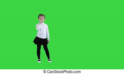 Cute happy girl singing into imaginary microphone on a Green Screen, Chroma Key.