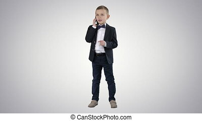 Cute little boy talking on his smartphone and standing in a dark suit on gradient background.