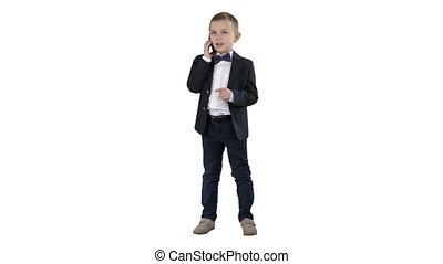 Cute little boy talking on his smartphone and standing in a dark suit on white background.